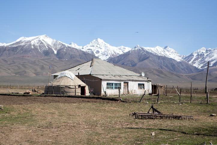 Haus vor den Bergketten des Tian-Shan-Gebirges
