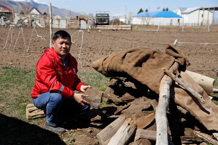 Foto: Freiwilliger kirgisischer Helfer zeigt Tierkot als Heizmaterial