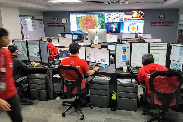 Rotkreuzbüro mit Monitoren, Wetterkarten und Mitarbeitenden