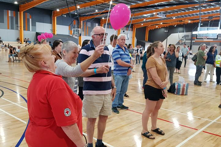 Foto: In einer Turnhalle hält ein älteres Pärchen Lufballons in der Hand. Daneben eine Rotkreuzhelferin