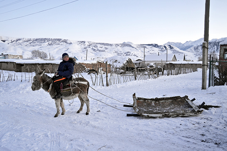 Foto: Kirgisischer Junge auf einem Esel mit selbst gebautem Schlitten
