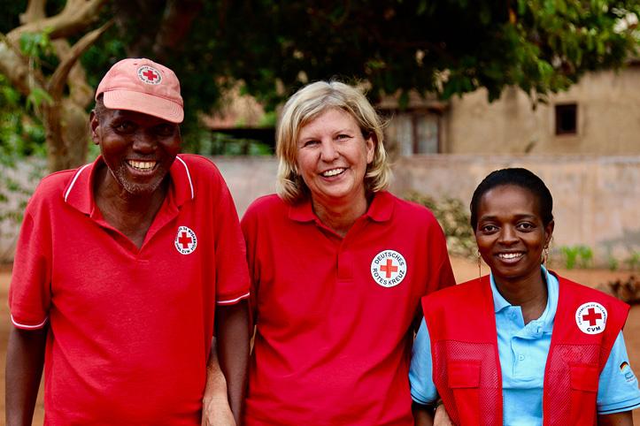 Drei Rotkreuz-Mitarbeitende, die lachen