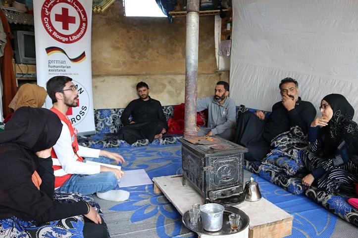 Rotkreuz-Helfer im Gespräch mit Menschen-Gruppe