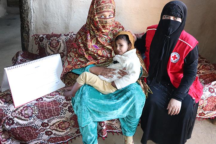 Ersthelferin in Pakistan mit Mutter und Kind