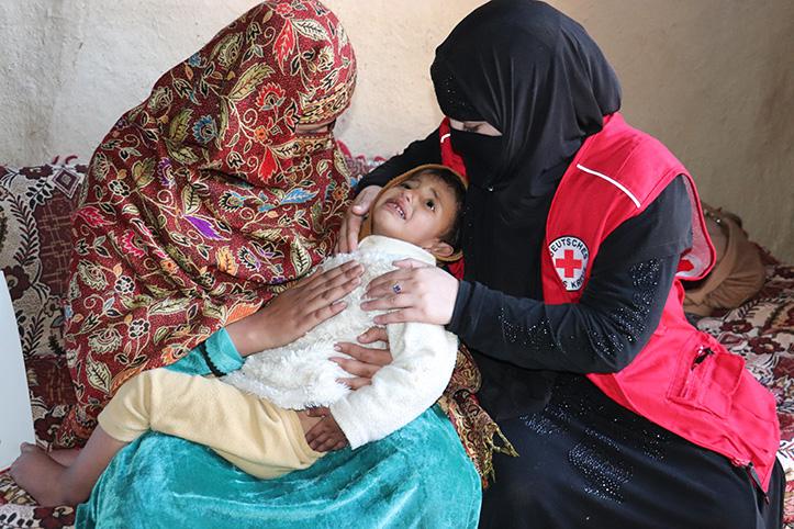 Pakistanische Ersthelferin versorgt Kind im Arm der Mutter