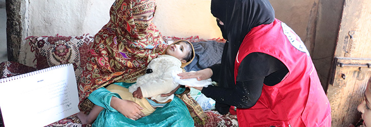 Erste Hilfe in Pakistan: Rothalbmondhelferin versorgt Jungen