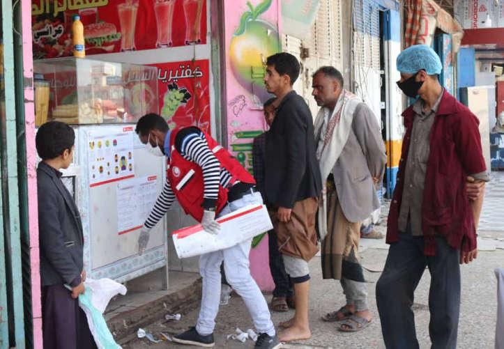 Helfer befestigt Plakat zur COVID-19-Aufklärung im Jemen