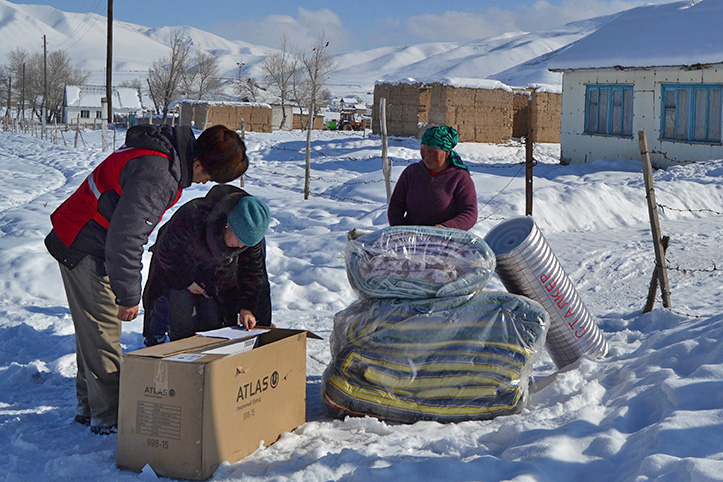 Kirgisische Witwe erhält im Schnee Hilfsgüter