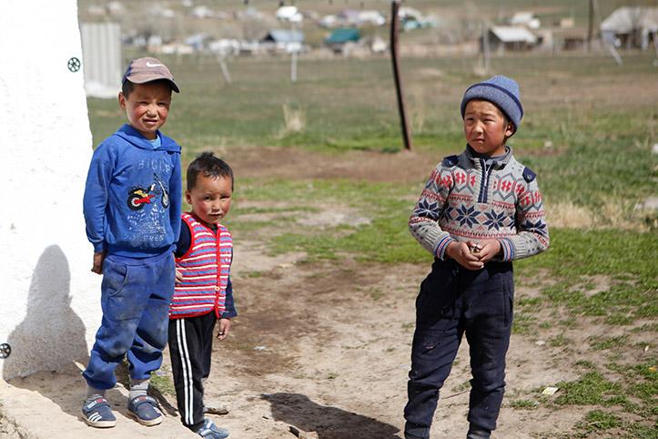 Drei kirgisische Jungs auf einer Wiese