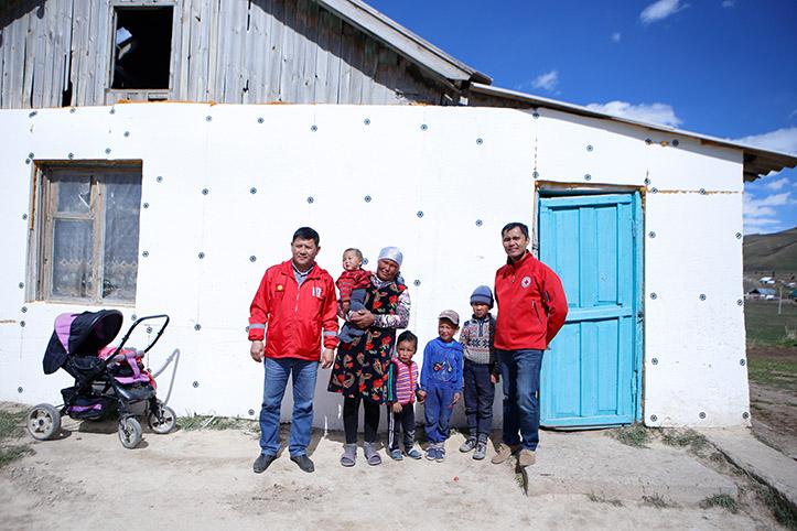 Kirgisische Familie mit Rothalbmondhelfern vor ihrem Haus