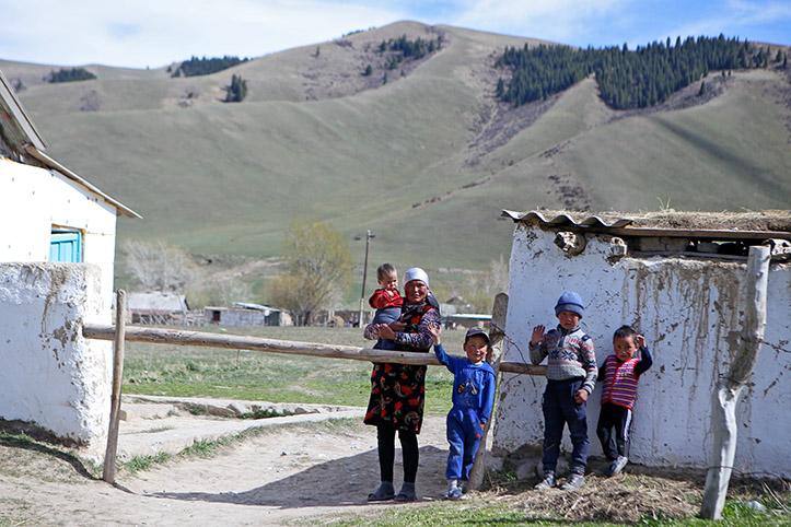 Kirgigische Mutter mit drei Kindern vor Bergen