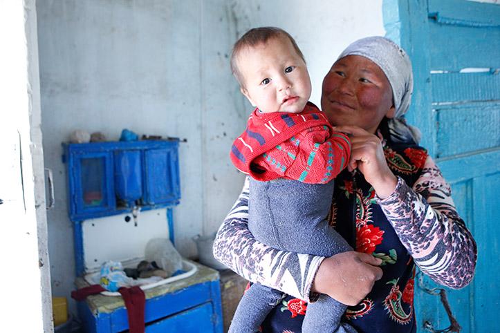 Kirgisische Witwe mit Baby in Küche
