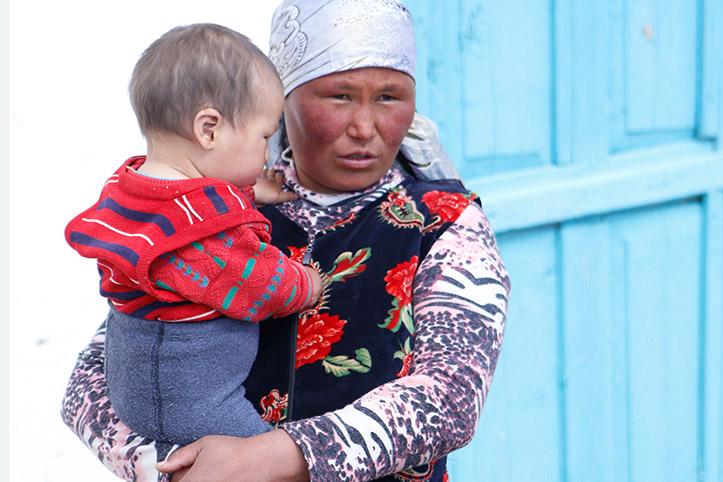 Kirgisin mit Baby auf dem Arm