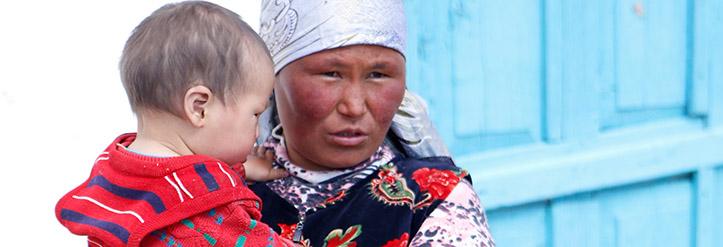 Kirgisische Witwe mit Baby auf dem Arm