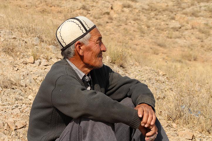 Senior sitzt in kirgisischer Steppe