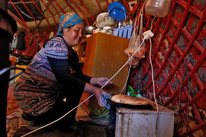 Kirgisin holt Fladenbrot aus dem Backofen einer Jurte