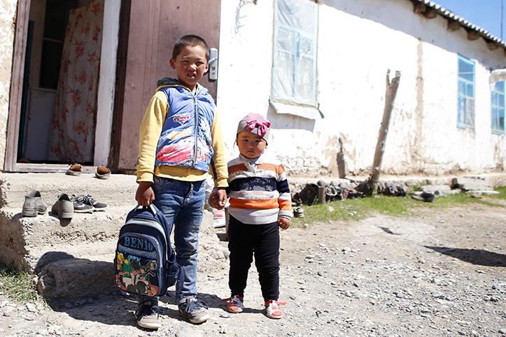 Zwei Kinder mit Rücksack vor einfachem Haus
