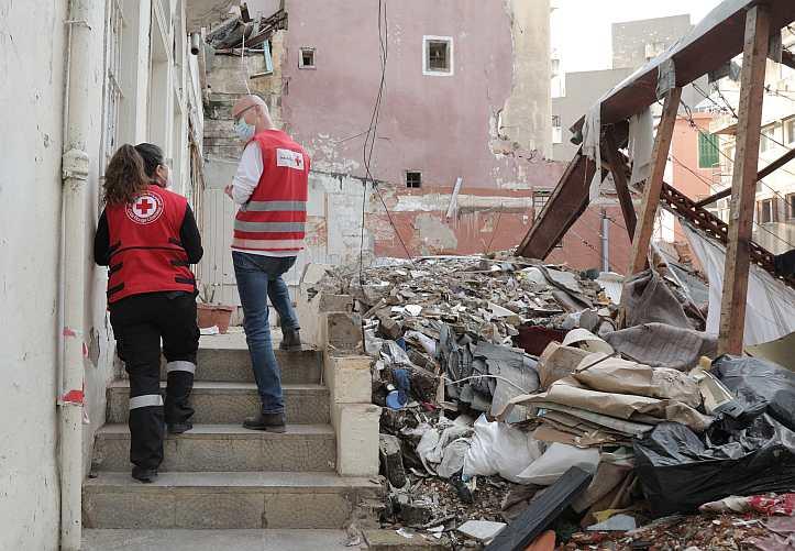 Rotkreuzmitarbeiter vor zerstörten Gebäuden