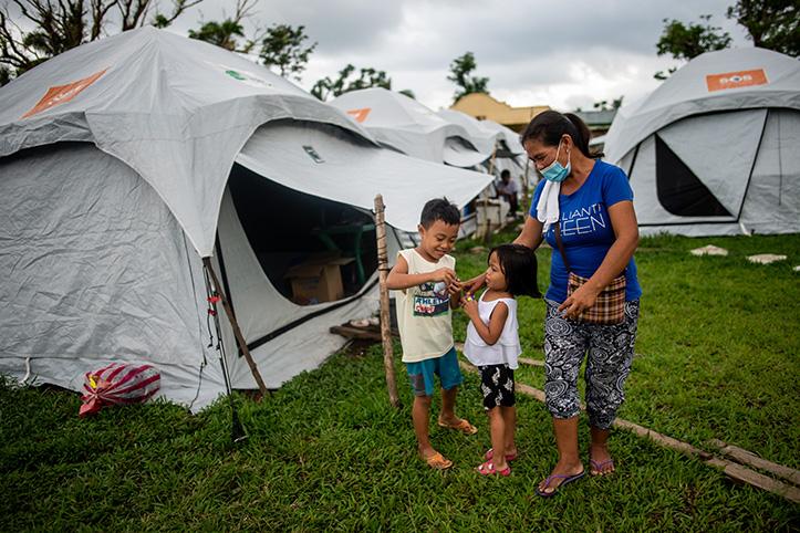 Philippinin mit 2 Kinder im Zeltlager