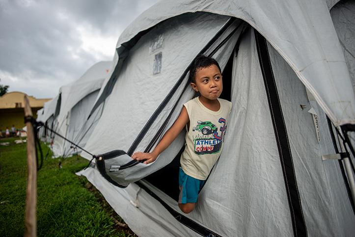 Pilippinischer Junge schaut aus einem Zelt
