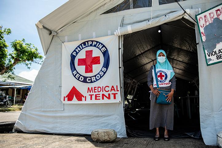 Freiwillige beim Philippinischen Roten Kreuz vor Sanitätszelt