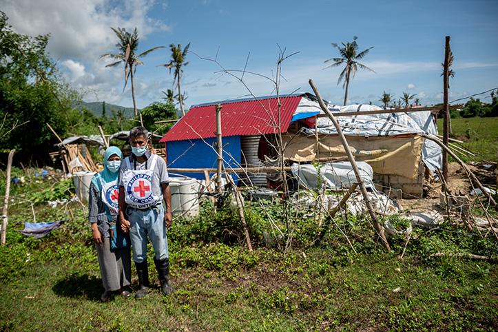 Freiwillige beim Philippinischen Roten Kreuz vor beschädigtem Haus