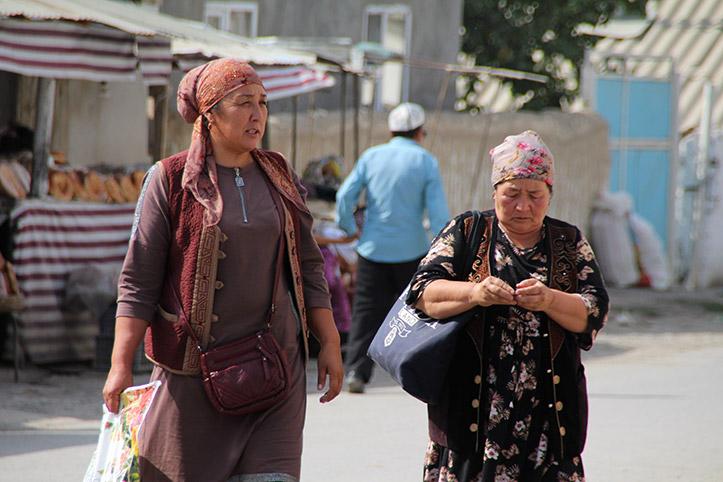 Kirgisische Frauen schlendern am Marktstand