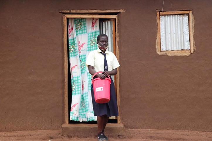 Ugandische Jugendliche mit Rotkreuz-Eimer