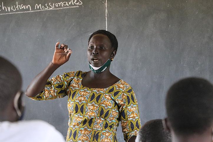 Portrait einer ugandischen Lehrerin vor der Tafel