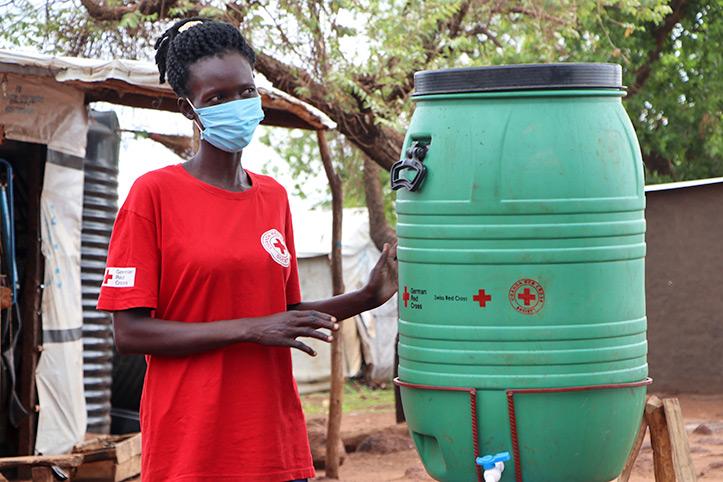 Ugandische Rotkreuzlerin lächelt neben Handwaschanlage