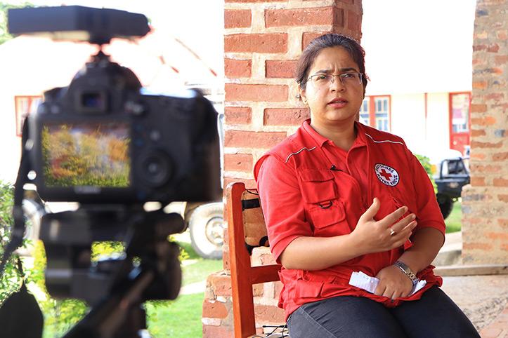 Rotkreuzmitarbeiterin in Uganda vor einer Kamera
