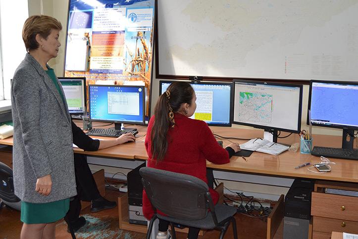 Kirgisische Wetterexpertin mit Kollegin vor Bildschirmen mit Wetterkarten