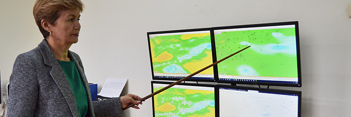 Kirgisische Wetterexpertin an Bildschirmen mit Wetterkarten