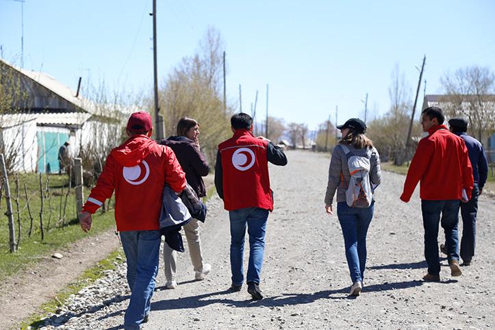 Rotkreuz- und Rothalbmond-Mitarbeiter laufen auf einer Dorfstraße