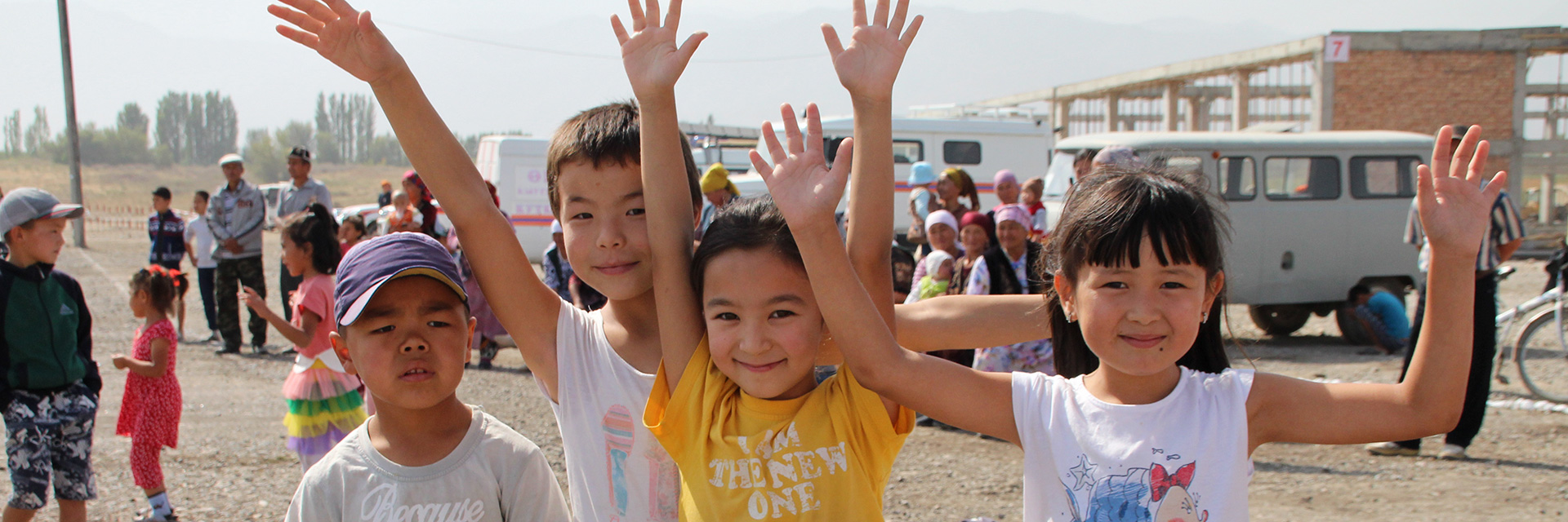 Kirgisische Kinder heben ihre Hände in die Luft